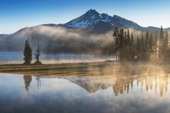 South Sister and Broken Top reflect over the calm waters of Sparks Lake at sunrise in the Cascades Range in Central Oregon, USA in royalty free stock image