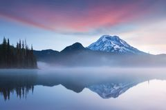 South Sister and Broken Top reflect over the calm waters of Sparks Lake at sunrise in the Cascades Range in Central Oregon, USA in stock image