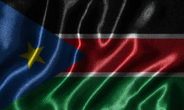 Wallpaper by South Sudan flag and waving flag by fabric. royalty free stock photo