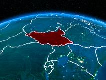 South Sudan from space at night. Orbit view of South Sudan highlighted in red with visible borderlines and city lights on planet Earth at night. 3D illustration Royalty Free Stock Photos