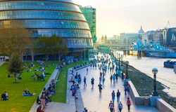 South walk of river Thames in sun set light. View includes a lot of walking people and London hall building Royalty Free Stock Photography