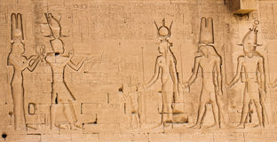 The south wall of the temple of Hathor at Dendera with lion-headed waterspouts. Cleopatra and her son Caesarian on the left side.  Royalty Free Stock Photo