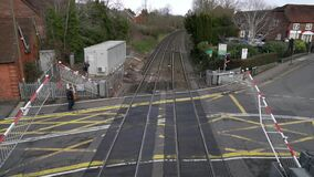 South Western Railway Train is Arriving to the Station and Crossing in Farnham, England. People And Vehicles are Going through the