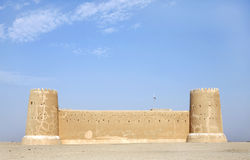 The South western wall of Zubarah fort, Qatar. The Zubarah Fort built in 1938 follows a traditional concept with a square ground plan with towers at the corner Royalty Free Stock Photo