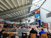 Southampton Airport terminal. Inside of terminal of Southampton Airport in England, UK, with people waiting and shops royalty free stock photos