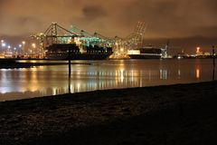 Southampton commercial container port by night. Moody sky illuminated by harbour lighting royalty free stock photos