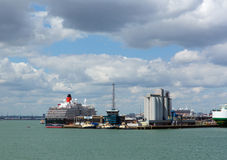 Southampton Docks with big cruise ship and cargo vessel on calm summer day with fine weather blue sky and white clouds Stock Photo