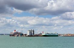 Southampton Docks with big cruise ship and cargo vessel on calm summer day with fine weather blue sky and white clouds Stock Images