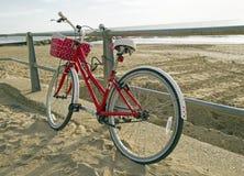 Southbourne, Bornemouth, Dorset, Inglaterra, opinião de A de uma bicicleta vermelha inclinou-se contra os trilhos Fotos de Stock Royalty Free