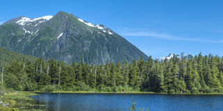 Southeast Alaska. Beautiful summer daytime panoramic of Heart Lake and Bear Mountain amidst the pine forests of southeast Alaska near Sitka Royalty Free Stock Image