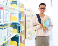 Southeast Asian adult student in library. Good looking Southeast Asian adult student in casual wear with school bag carrying text books standing inside school Stock Image