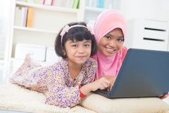 Southeast Asian children surfing internet. At home. Malay Muslim girls Royalty Free Stock Images