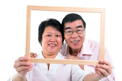 Southeast Asian couple. Smiling old Southeast Asian couple looking through an empty frame, isolated on white background Royalty Free Stock Images