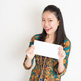 Southeast Asian female hand holding white paper card. Portrait of young southeast Asian girl in traditional Malay batik kebaya dress hand holding a white blank Royalty Free Stock Images