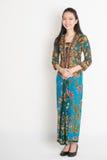 Southeast Asian girl. Full length Southeast Asian female in batik dress standing on plain background Stock Photography