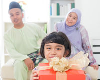 Southeast Asian girl with gift box. Muslim family living lifestyle. Happy smiling Malay parents and child Stock Photography