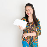 Southeast Asian girl hand holding white paper card. Portrait of young southeast Asian woman in traditional Malay batik kebaya dress hand holding a white blank Royalty Free Stock Image