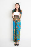 Southeast Asian girl hand holding a white paper card. Portrait of young southeast Asian woman in traditional Malay batik kebaya dress hand holding a white blank Royalty Free Stock Photo