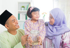Southeast Asian Malay family saving money. Islamic banking concept. Southeast Asian Malay family saving money at home. Muslim father, mother and daughter living Stock Image