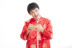 Southeast Asian male in cheongsam hands holding red packets , ang pow ,  on white background. Stock Photography