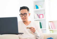 Southeast Asian male online shopping. Southeast Asian male holding credit card online shopping at home Royalty Free Stock Image