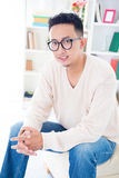 Southeast Asian male with spectacles. Sitting on sofa at home, indoor living lifestyle Stock Image