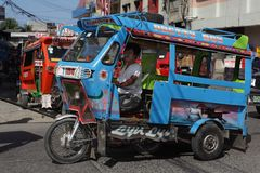 Southeast-Asian motorela on street. Southeast-Asian motorela in action on city street. A motorela (motorcycle + caretela)  is a unique form of local short haul Stock Image