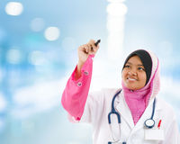 Southeast Asian Muslim medical student. Sketching on transparent screen, hospital blue background royalty free stock photo