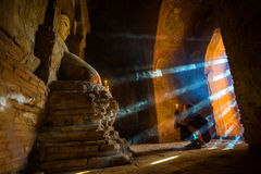Southeast Asian neophyte praying with candle light in a Buddihist temple Stock Photo