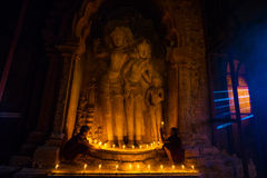 Southeast Asian neophyte praying with candle light in a Buddihist temple Royalty Free Stock Photos
