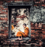 Southeast Asian Novice monk reading book stock photography
