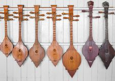 Ancient instrumental. Southeast asian style lute instrumental hang on white wall Stock Photography