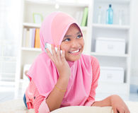 Southeast Asian teenager talking on phone. Southeast Asian teenager on the phone at home. Muslim teen girl living lifestyle Royalty Free Stock Photo
