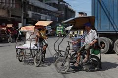 Southeast-Asian tricycles on urban street. Two Southeast-Asian tricycles waiting and barting on a busy urban street for passengers. A tricycle is a unique form stock photo