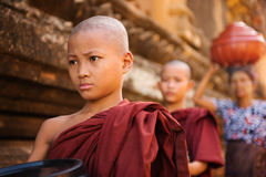 Southeast Asian young Buddhist monks walking morning alms. In Old Bagan, Myanmar Stock Photo