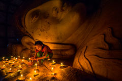 Southeast Asian young girl praying with candle light in a Buddhist temple Royalty Free Stock Photography