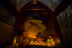 Southeast Asian young girls praying with candle light in a Buddihist temple Stock Photography