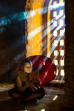 Southeast Asian young monk reading a book in a Buddhist temple Stock Photo