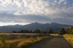 The Southern Alps New Zealand. A road, bathed in golden evening sunlight, leads upto the Southern Alps on New Zealand's South Island royalty free stock images