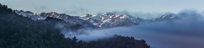 Southern Alps. Panoramic Composition Of Southern Alps With Misty Rain Forest In Foreground, From Lake Mapourika, Westland Tai Poutini National Park, West Coast Royalty Free Stock Photos