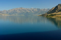 Southern Alps reflecting in lake Hawea Stock Image