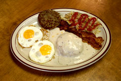 Southern Breakfast Platter 2. Another look at a traditional southern breakfast with biscuits and gravy, bacon, hashbrowns, sausage patty and two fried eggs Royalty Free Stock Image