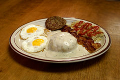 Southern Breakfast Platter. Traditional southern breakfast with biscuits and gravy, bacon, hashbrowns, sausage patty and two fried eggs Stock Image