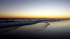 Southern California beach at dusk. Late summer dusky skies signal the end of a day in Huntington Beach, CA Royalty Free Stock Photo