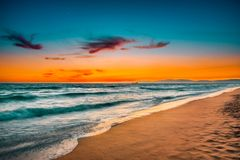 Southern California Beach at Sunset. Manhattan Beach  at sunset with a jetty in the foreground Royalty Free Stock Photo