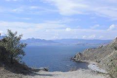 Southern coast of Crimea's peninsula near Feodosia in Ukraine. Beach with tourists on a background a mountain Kara-Dag Stock Image