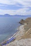 Southern coast of Crimea's peninsula near Feodosia. In Ukraine: beach with tourists on a background a mountain Kara-Dag Stock Photos
