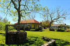 Southern Farmhouse. Two small houses with oak trees and a brick well on the green grass on a Louisiana plantation stock photos
