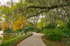 Southern Garden Walkway. Paved brick path with live oak trees and spanish moss beside a water feature in New Orleans royalty free stock photo