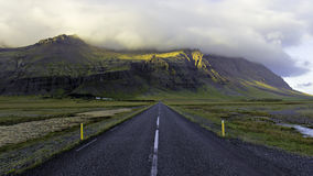 Southern Iceland Ring Road. Looking down middle of empty road heading straight towards towering cliffs shrouded with low cloud royalty free stock photos